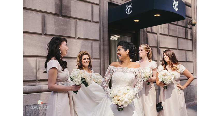 South Asian bride in white lace off the shoulder gown outside the Yale Club in NYC, springtime, with bridesmaids
