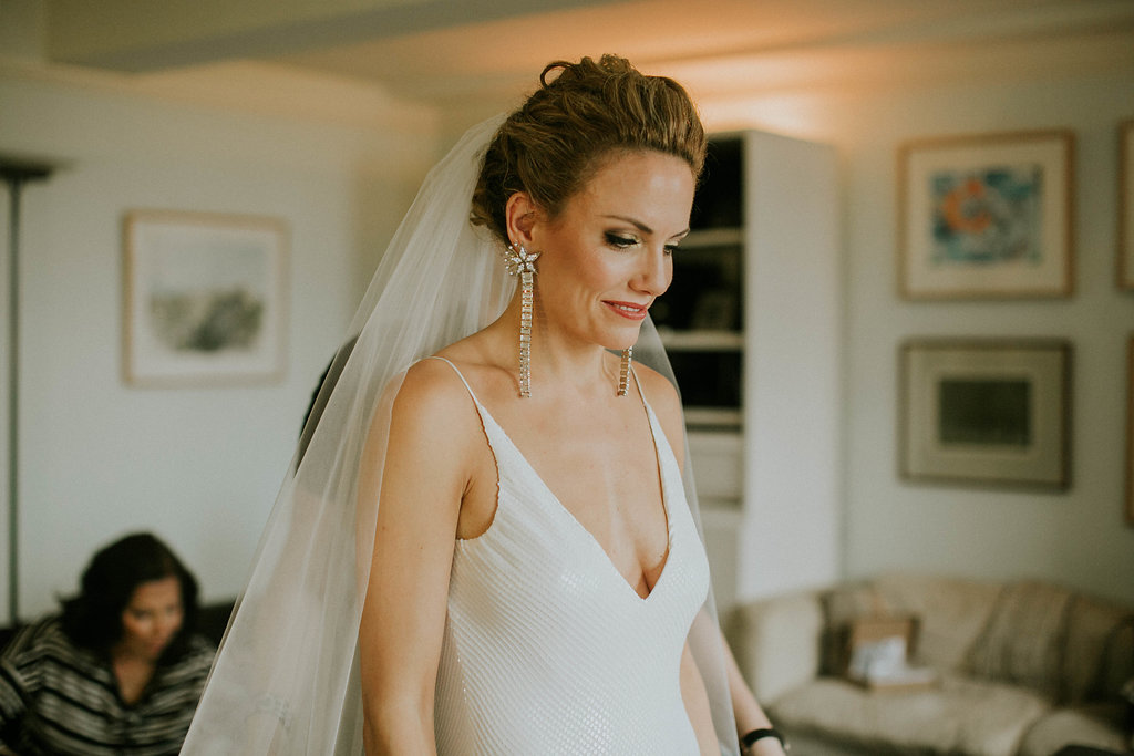 Bride with natural curls swept into romantic chignon with disco glam makeup and long earrings, in Brooklyn Heights, New York
