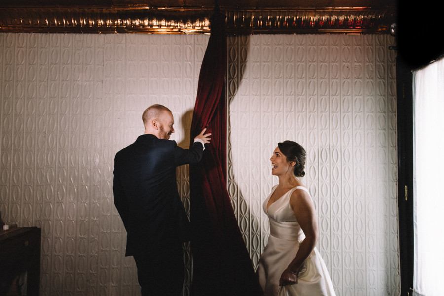 Bride with romantic updo and soft lashes greets groom in kilt at Green Building in Brooklyn, New York