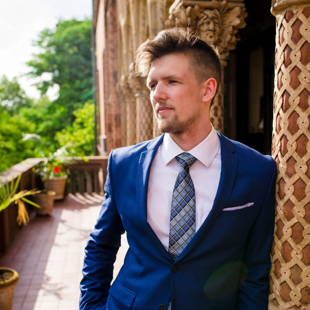 dj coolhand in dark teal suit with gradient blue tie on balcony, trees in background