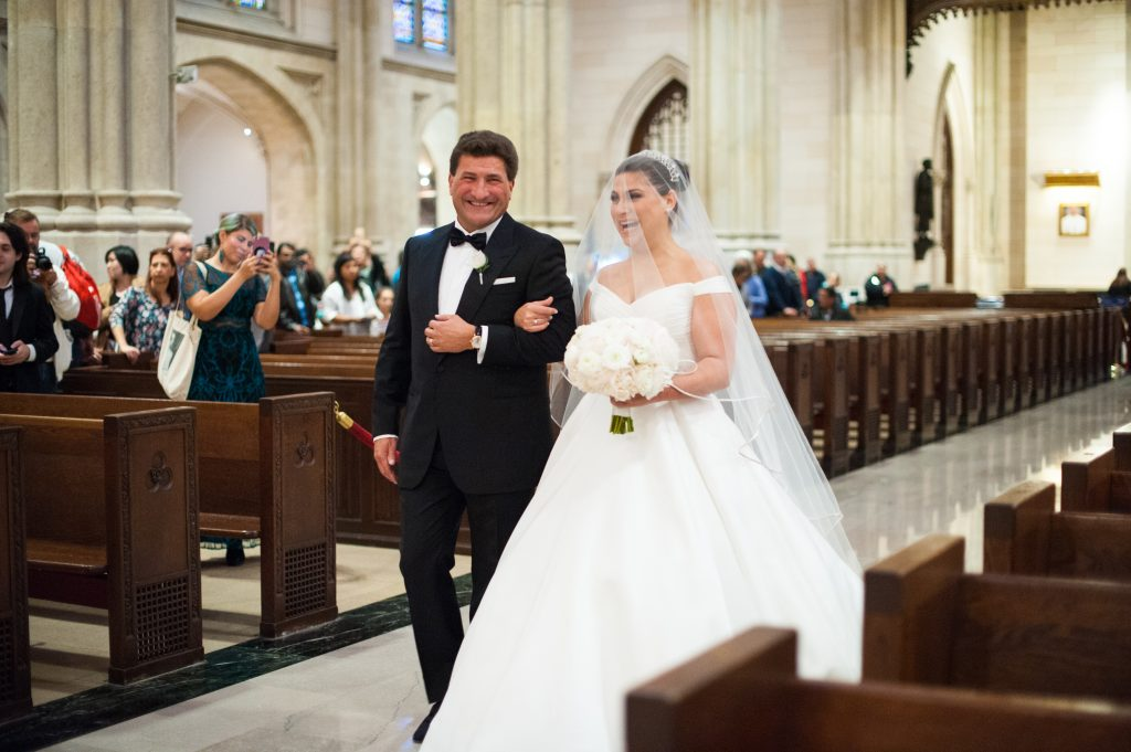 bride and father walking down aisle smiling