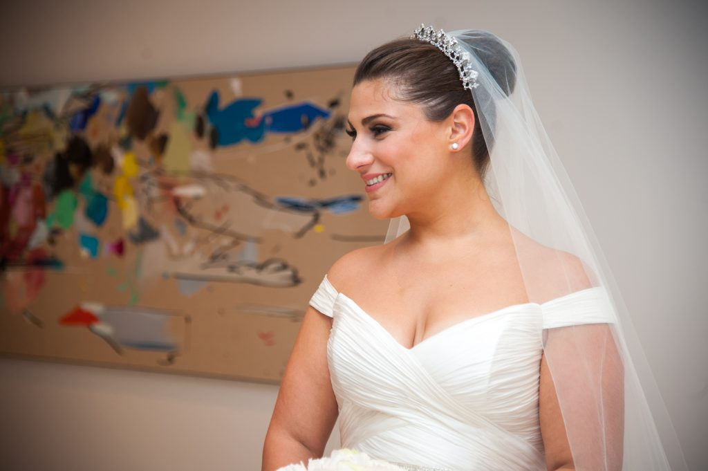 bride in makeup and gown, profile shot in front of painting
