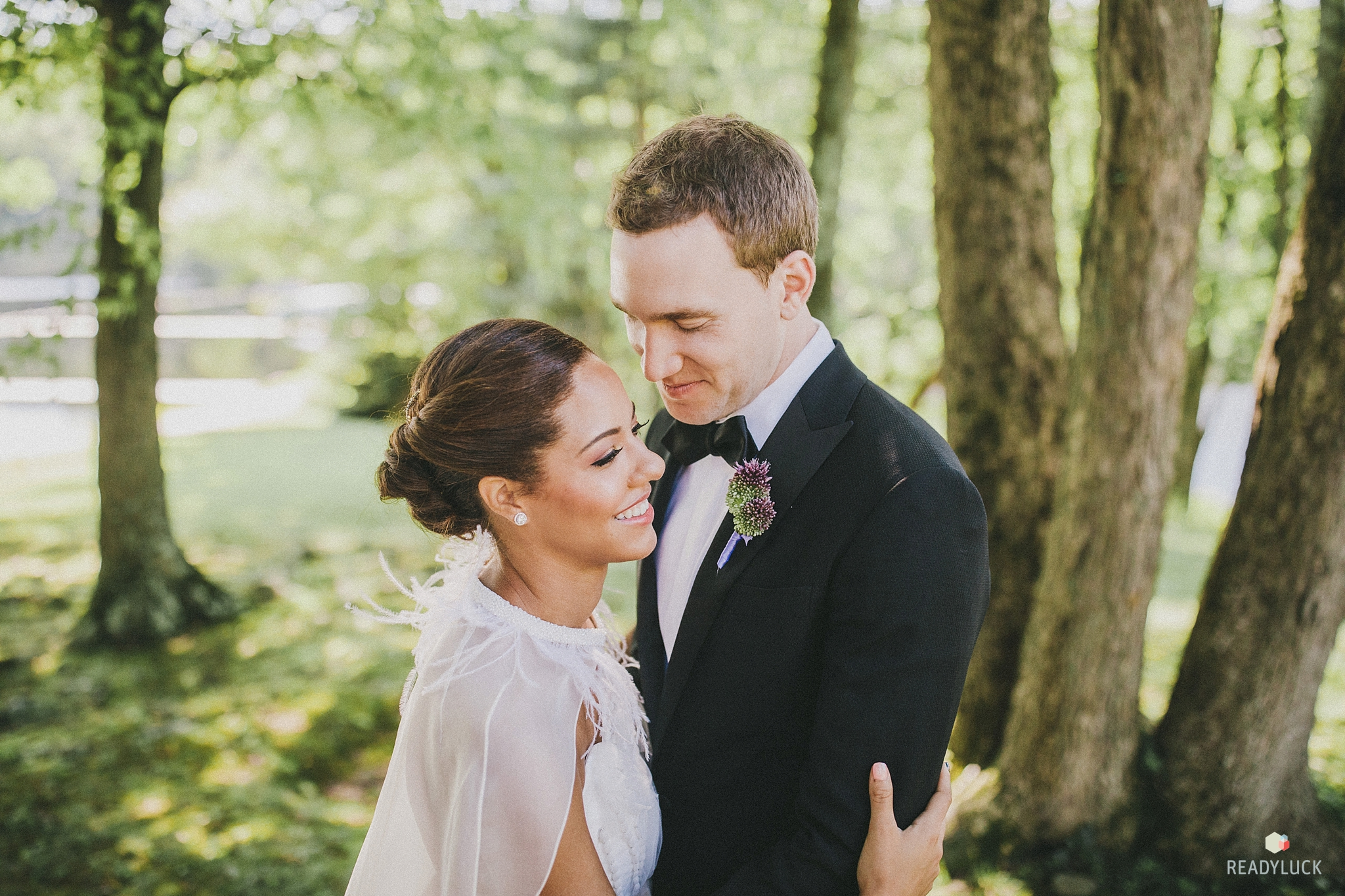 Bride with feathered cape and modern chignon hugging groom on wedding day at Cedar Lakes Estate
