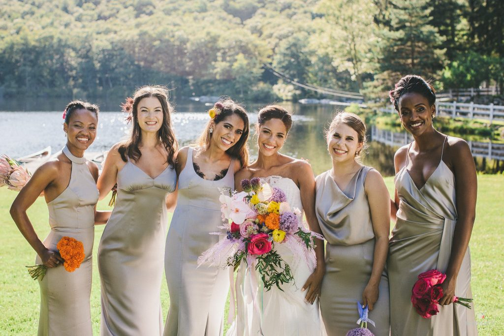 wedding party portrait of bride and bridesmaids with lake and countryside vista