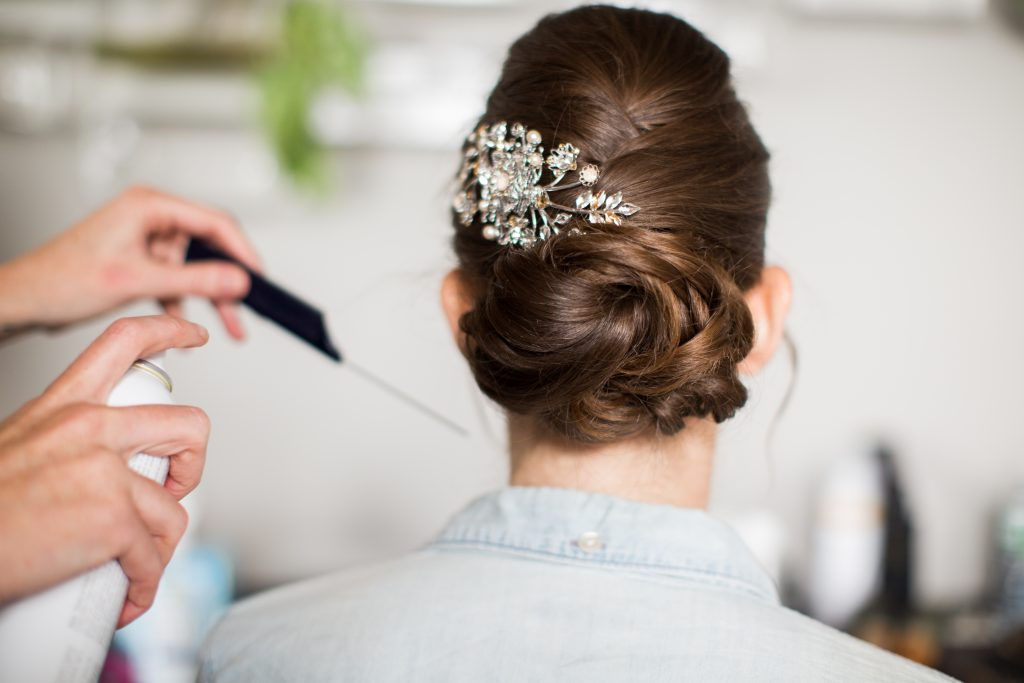 Bridal up-do with textured hair pulled into a bun, adorned with floral sparkly hair accessory
