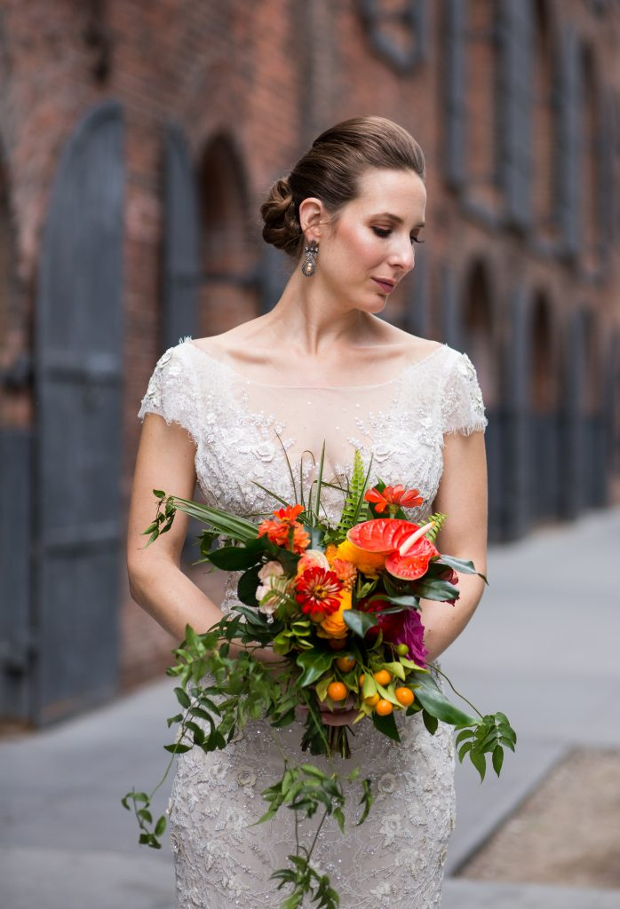 Bridal portrait in cream gown, tropical bouquet with anthuriums and other orange, red and magenta flowers, as well as long greenery that drapes down past brides' grasp