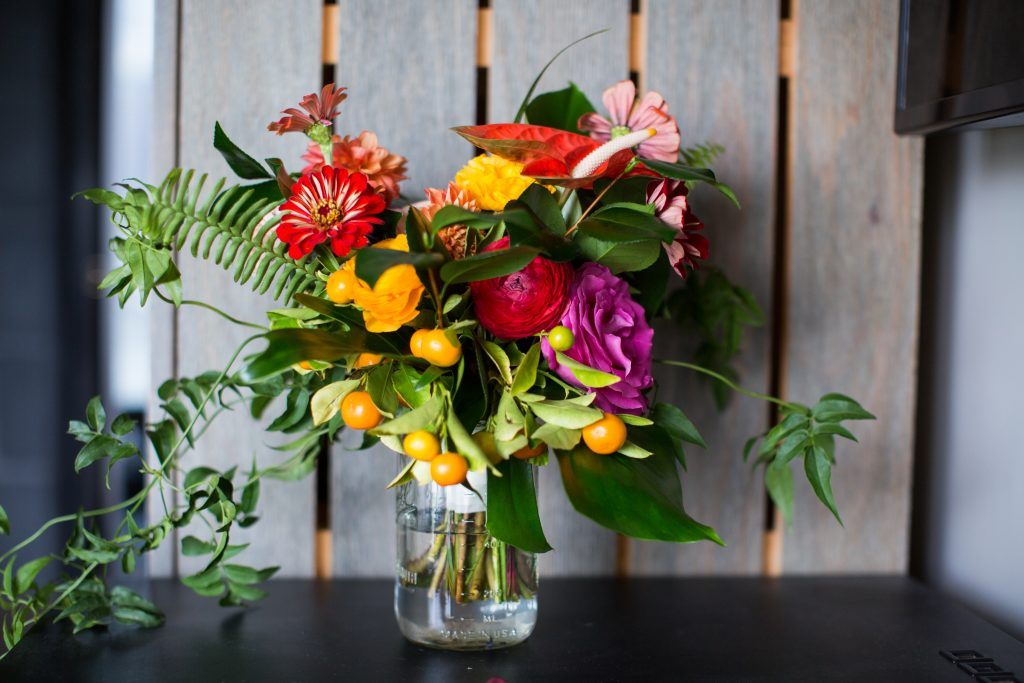 Tropical bouquet with yellow, red and magenta blossoms, fern greenery that drips onto the table, all in a science beaker vase