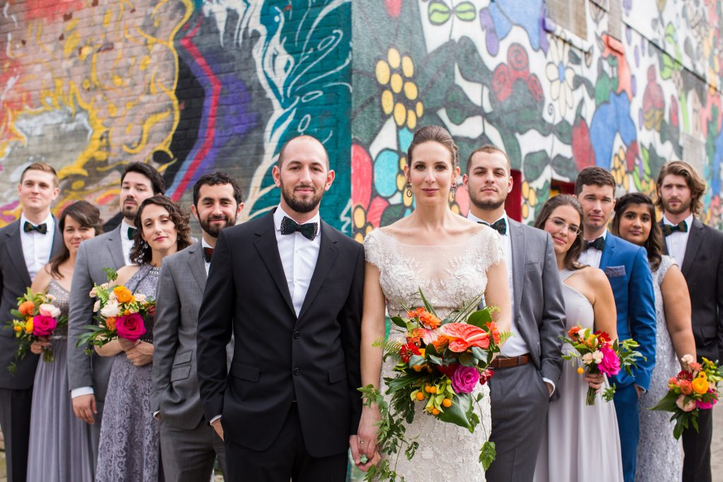 full wedding party portrait, bride and groom front and center. the rest of wedding party fans out behind them in suits of grey, blue or black, grey dresses.