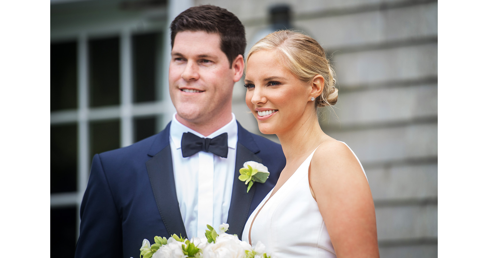 bride in white dress and white bouquet, groom in navy suit and white boutonnière