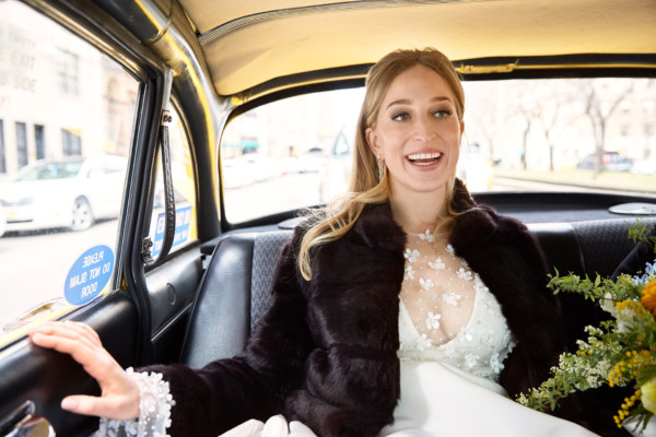 Blonde bride in Oscar de la Renta gown and Mimosa Flowers in taxi outside New York Historical Society before her wedding