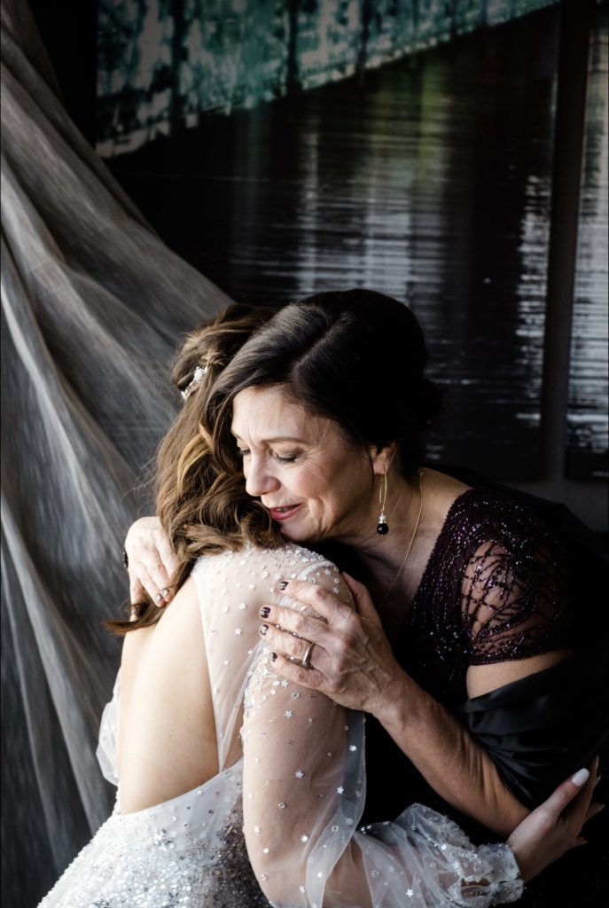 Bride faces away, open back wedding gown and silver sequins. Mother of the bride in a dark beaded dress. She holds her daughter with a bittersweet embrace. Dark background with water.