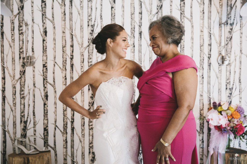 Bride grins at mom on left with updo and strapless, geometric textured white gown. Mother of the bride on the right, fuchsia wrap front dress, smiling at her daughter.