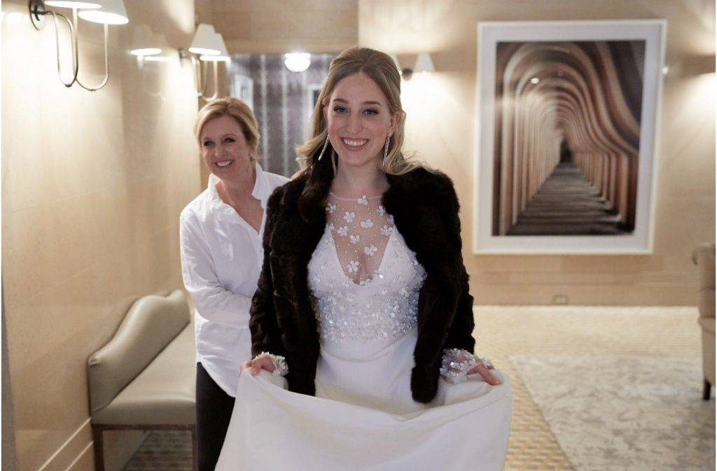 Blonde bride in white gown and black jacket and mother of the bride behind her smiling, hotel room.