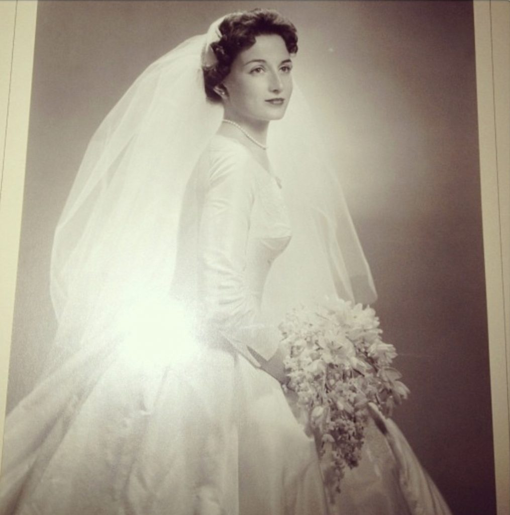 Black and white bridal portrait, Sharon's mother with wavy dark hair, 3/4 angle. Long veil, full skirt, big bouquet.
