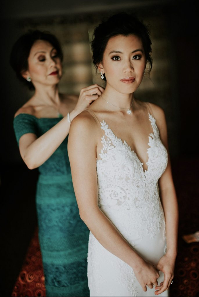 Bride with smokey eyes and white applique dress with transparent straps. Mother of the bride behind in soft focus, with dramatic makeup and red lips, dressed in jade green.