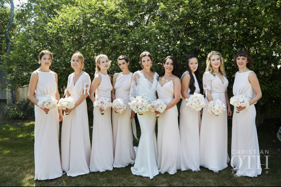 Bride with her seven bridesmaids, all with different hairstyles, posing at Crow's Nest in Montauk