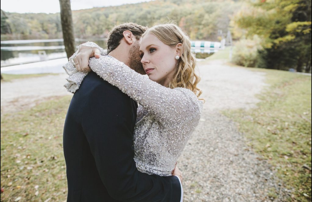 Bridal portrait, bride with wedding makeup, blonde waves, groom in tuxedo. Woods and lake in the background.