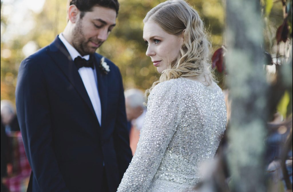 Groom on the left, black and white in tuxedo, blonde waves on the bride with spangled dress. In the woods.
