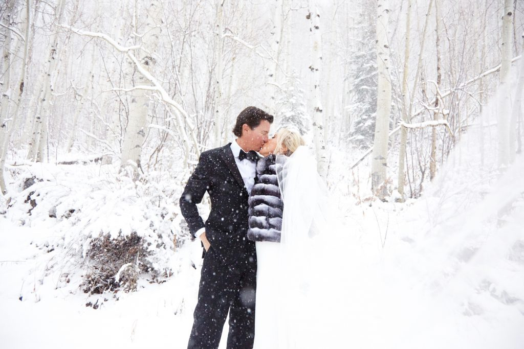 Bride and groom kissing in a winter wonderland - snowy background and trees