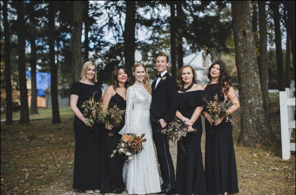 Wedding portrait, wedding party, bridesmaids, bride in white sparkly gown. Woods in background.