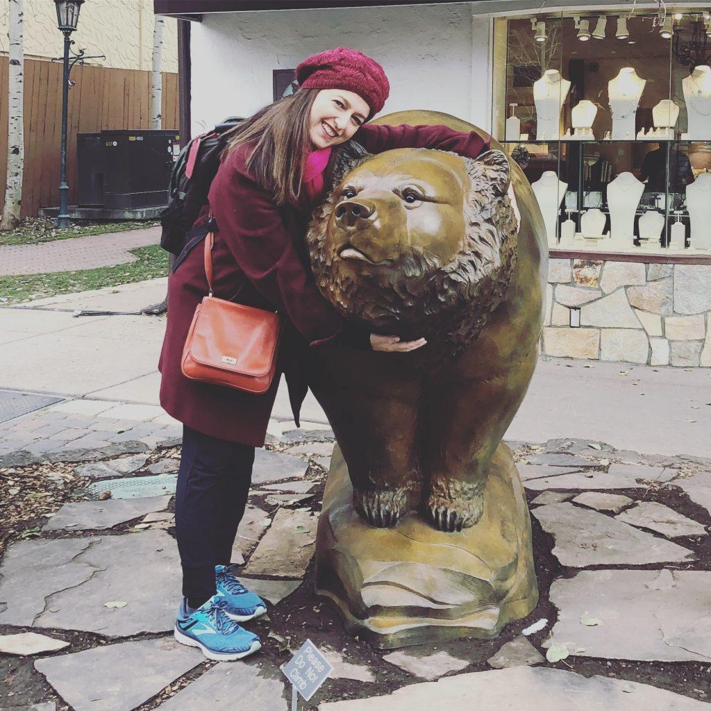 Sharon Becker, makeup artist, outside hugging a bear statue