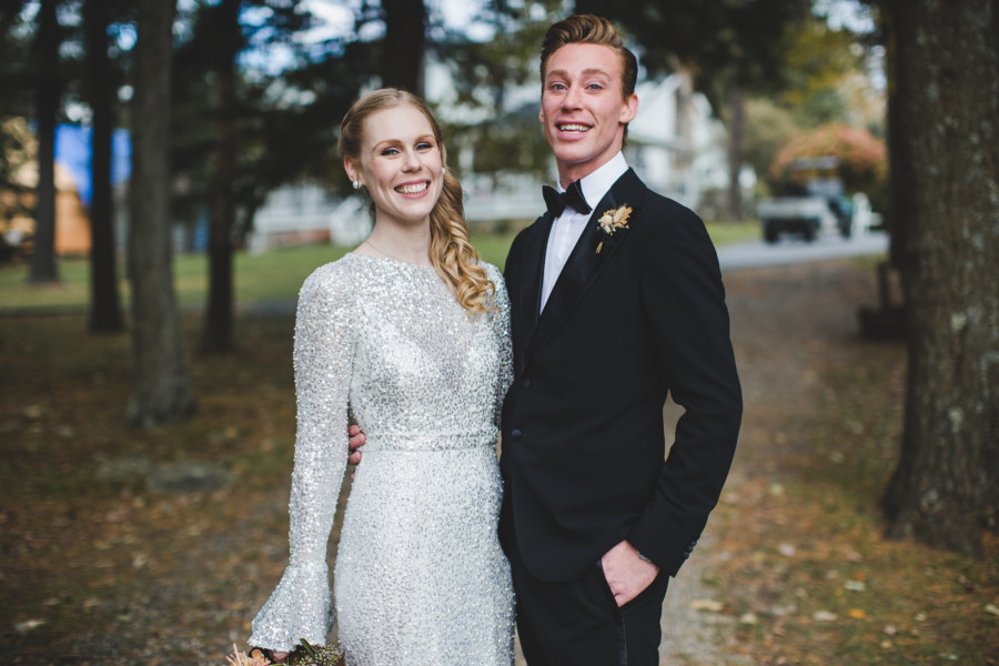 Blonde bride with modern Hollywood waves and fully beaded gown poses with her best man at Cedar Lakes Estate before wedding