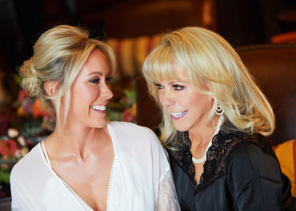 blonde bride in white prep gown, her mother next to her, both looking at each other smiling