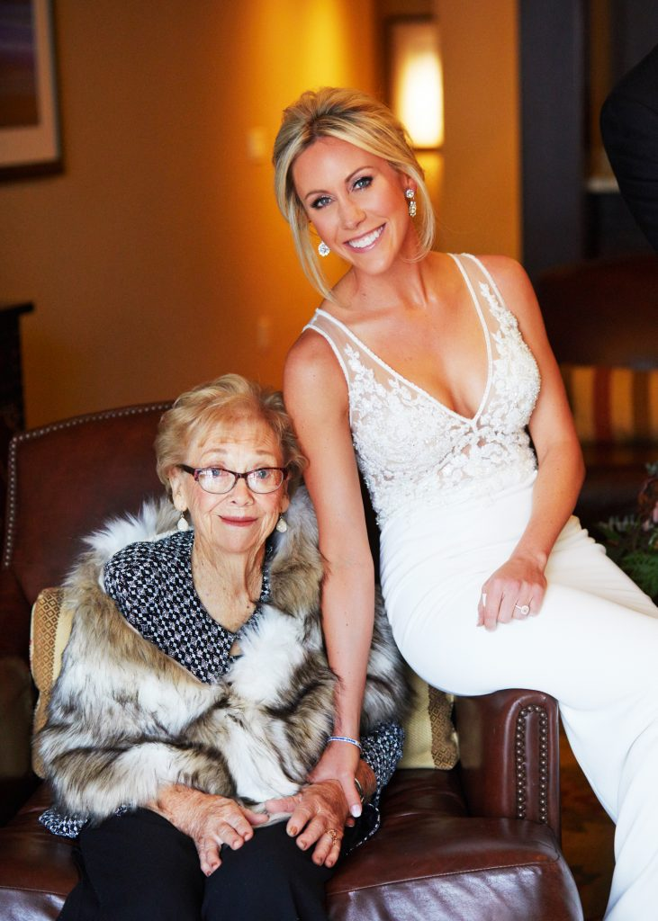 Bridal portrait, blonde bride in white lacy gown with lace inset in bodice. Gram next to her with glasses, red lipstick and a fur stole.