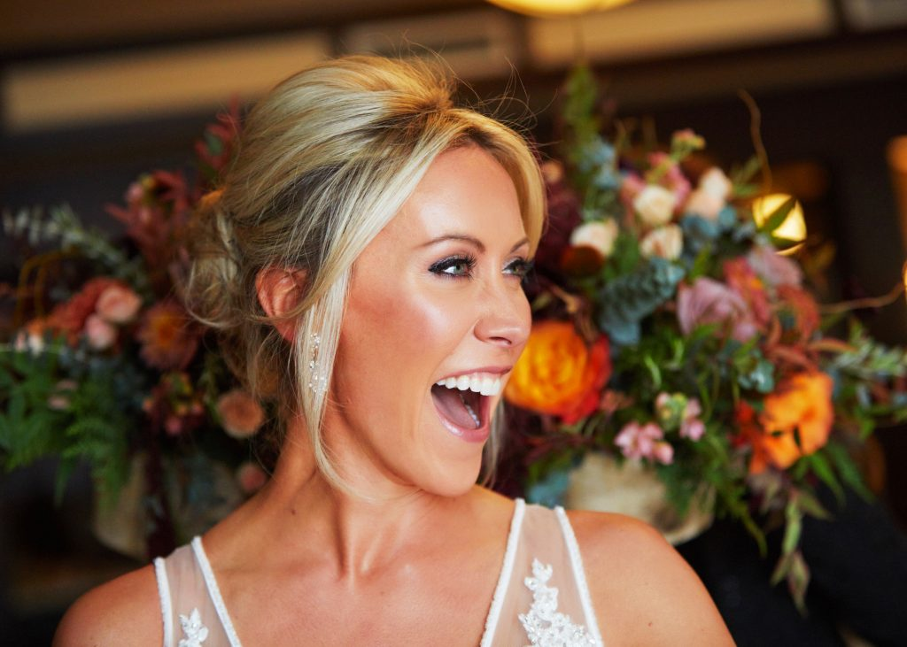 Bride looking to the right, blonde hair in glamorous updo, mouth open in big smile. Big bouquet behind her, orange and white blooms with green fronds and ferns.