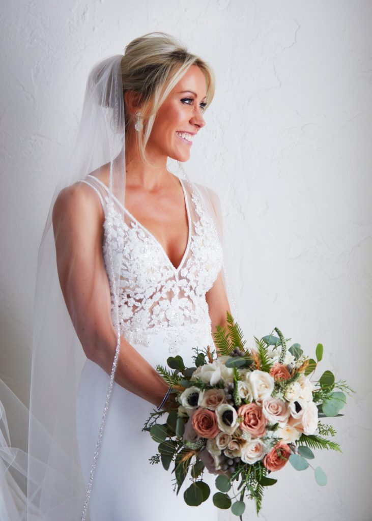 three-quarters portrait of bride in white lacy gown and veil. White and blush blooms of her bridal bouquet with little green drops popping out.