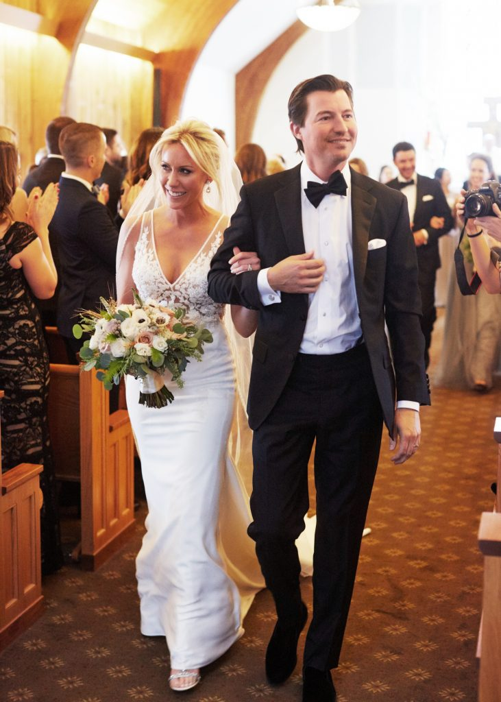 Bride and groom walking down the aisle, white lacy bridal gown and classic black tuxedo.