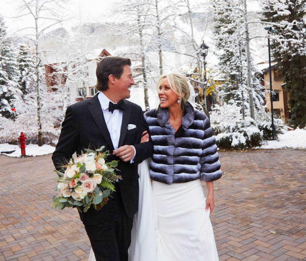 Bride and groom outside in the snow, arm in arm, groom with wedding bouquet in hand. Bride has puffy short jacket on, they're smiling and looking at each other.