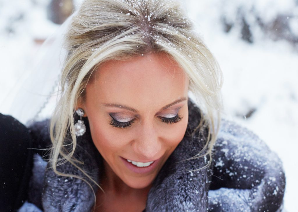 Closeup shot from above, bride looking down with a dusting of snow in her hair, silver eyeshadow and long lashes visible.