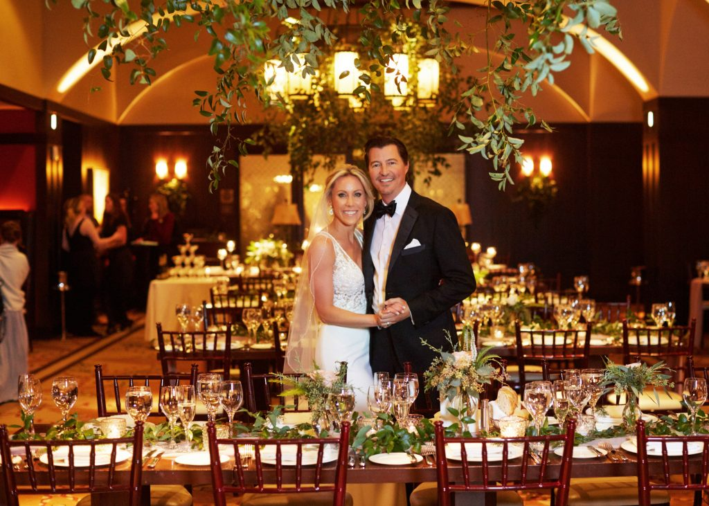 Bride and groom in banquet hall, warm lighting and green centerpieces