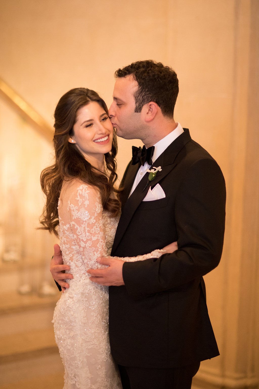 Beautiful bride with long dark hair waved and pulled half back off her her face, with her groom at the Plaza Hotel in New York City