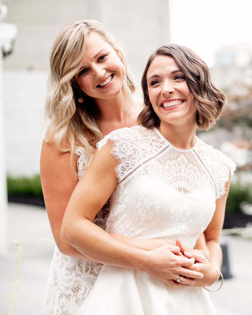 Two brides, one with a dark bob length hair and one with long blonde hair, with modern, edgy textured waves, posing in DUMBO, Brooklyn, on wedding day