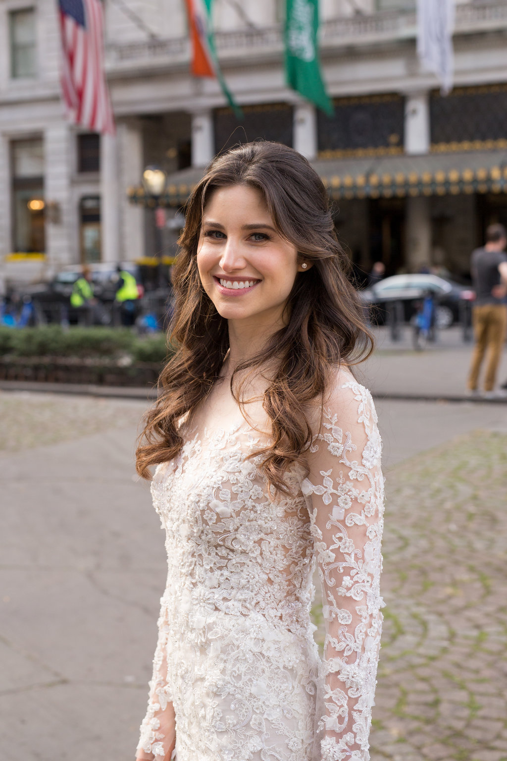 Beautiful bride with long dark hair that is waved and pulled half back off her face, posing at Plaza Hotel in New York City