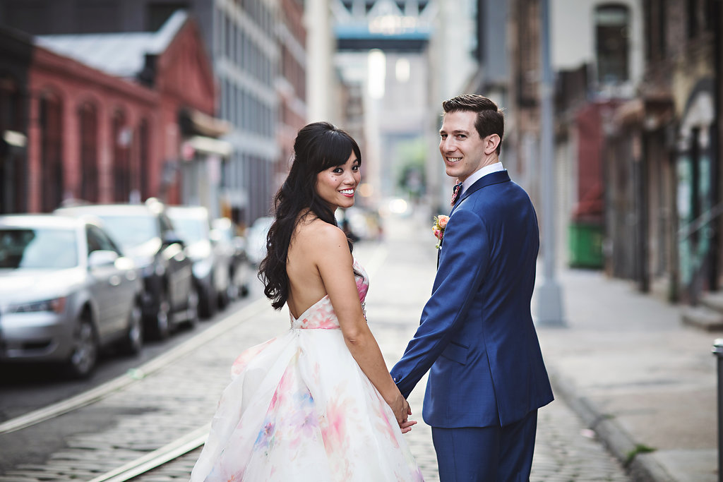 Bride with long dark hair pulled half up and waved posing in DUMBO, Brooklyn, on wedding day