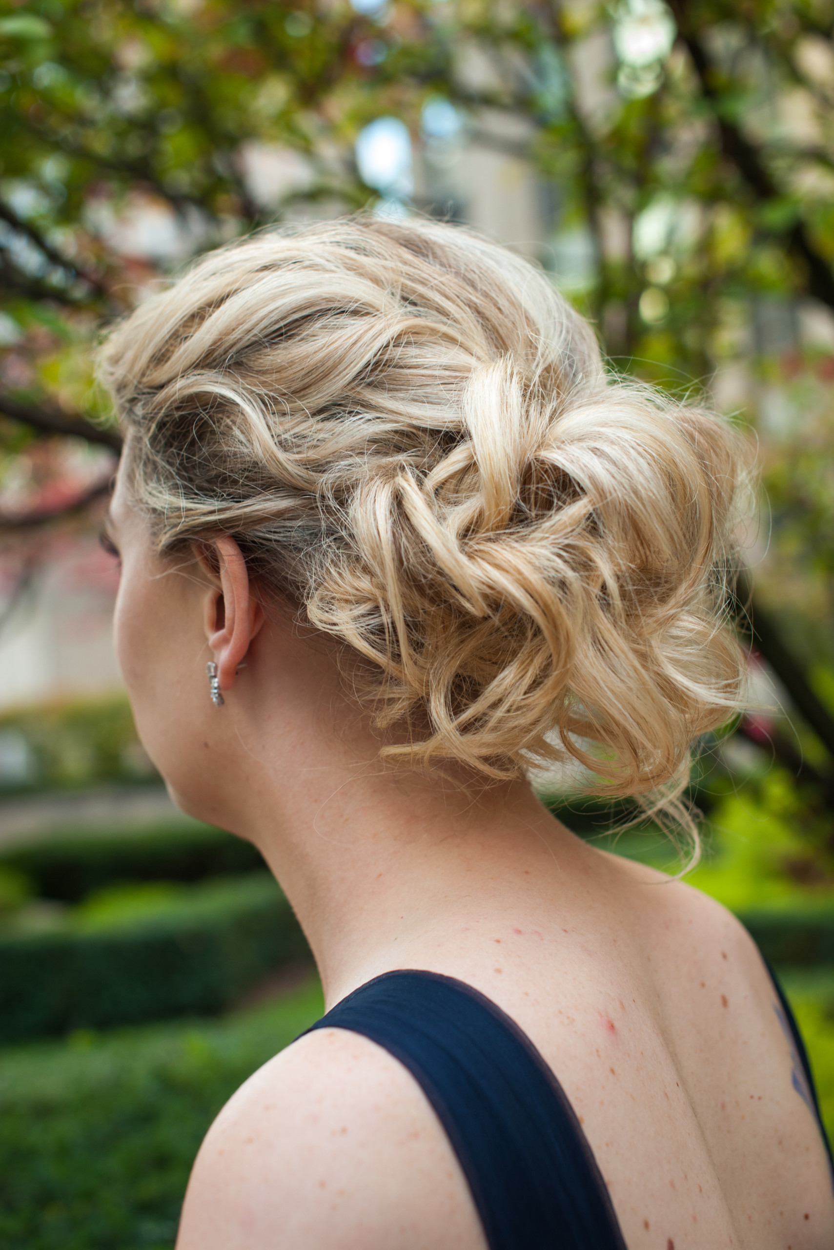 Bridesmaid with blonde hair swept up in loose, romantic, modern updo pictured at 620 Loft & Garden in Rockefeller Center, New York City