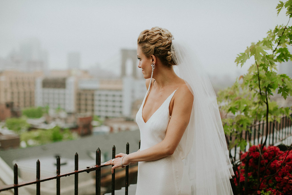 Chic bride with her curly hair swept up into low chignon, looking out over Brooklyn Heights in her A La Robe gown and veil
