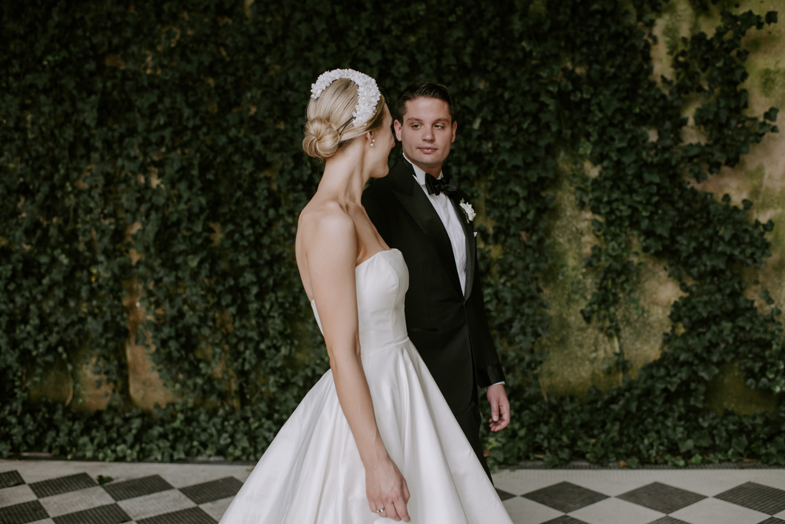 Modern elegant bride with blonde hair swept into chic modern chignon with flowered headband, pictured at Oheka Castle