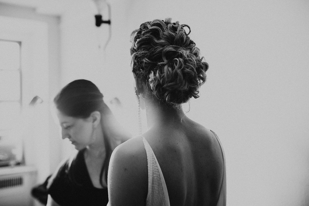 bride with curly hair swept up into low chignon with natural texture gets makeup touchup from Sharon Becker of SB Beauty