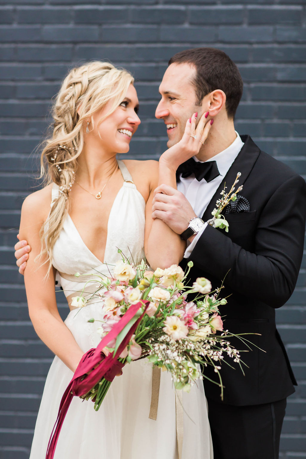 Cool modern bride with romantic braid in her blonde hair, pictured with groom at Wythe Hotel in Brooklyn
