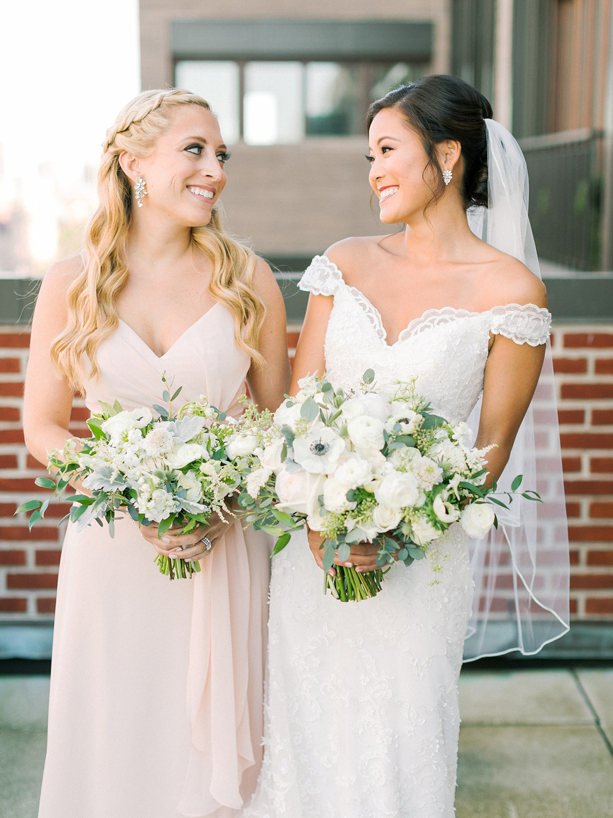 Bridesmaid with wavy blonde hair and bride with modern updo