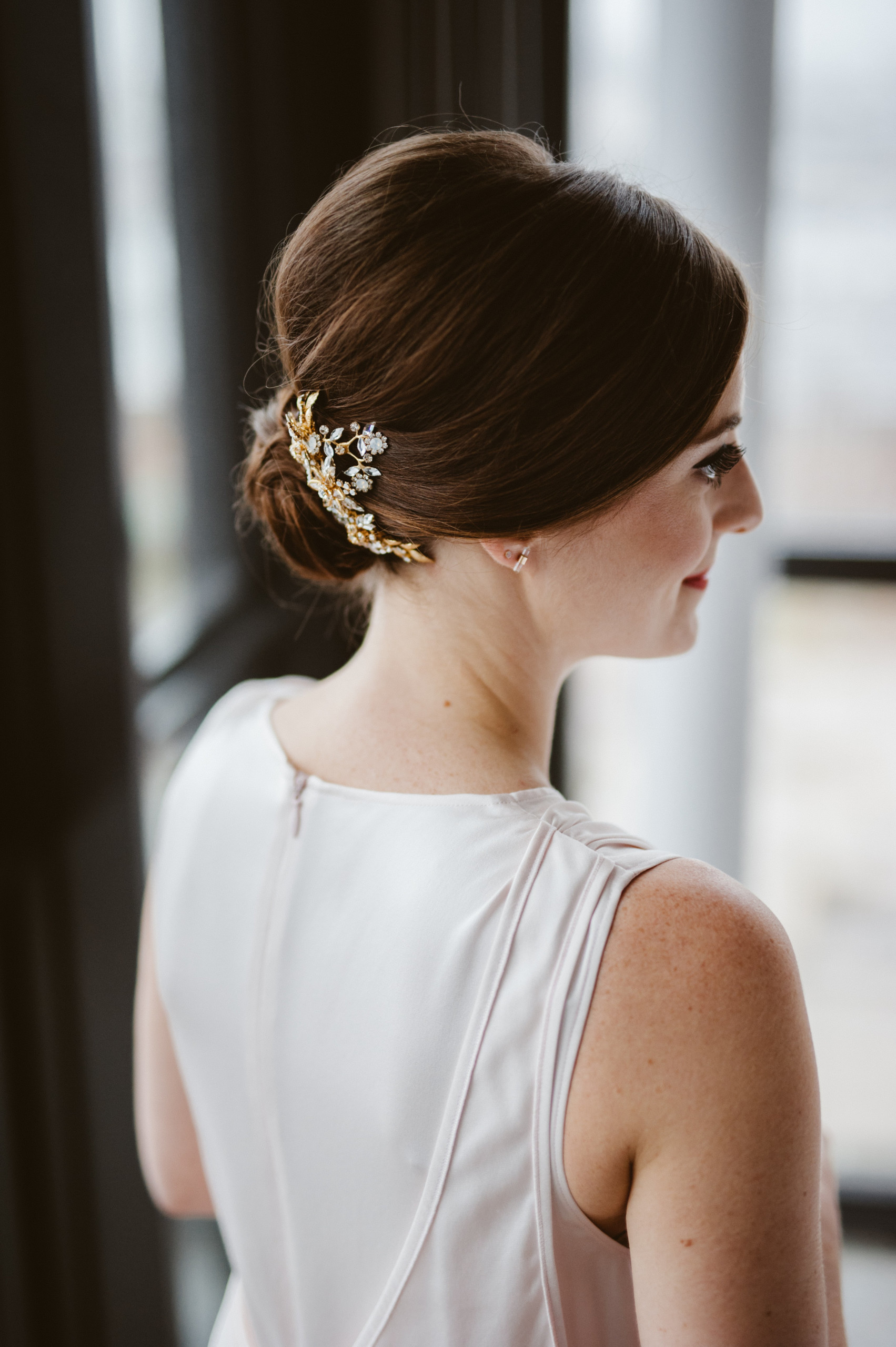 Bride with auburn hair styled into modern classic chignon with modern hair accessory, pictured at the Wythe Hotel in Williamsburg, Brooklyn