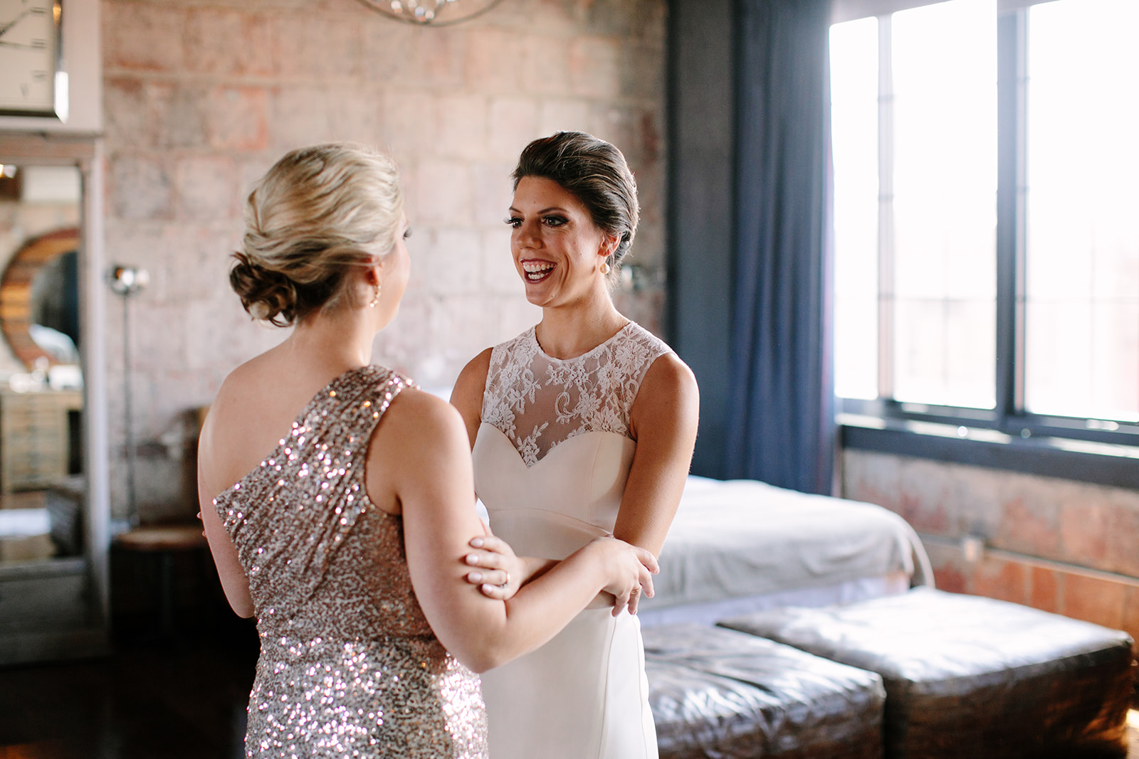 Bride and sister, both with chic modern updos, pictured at the Paper Factory Hotel in Long Island City
