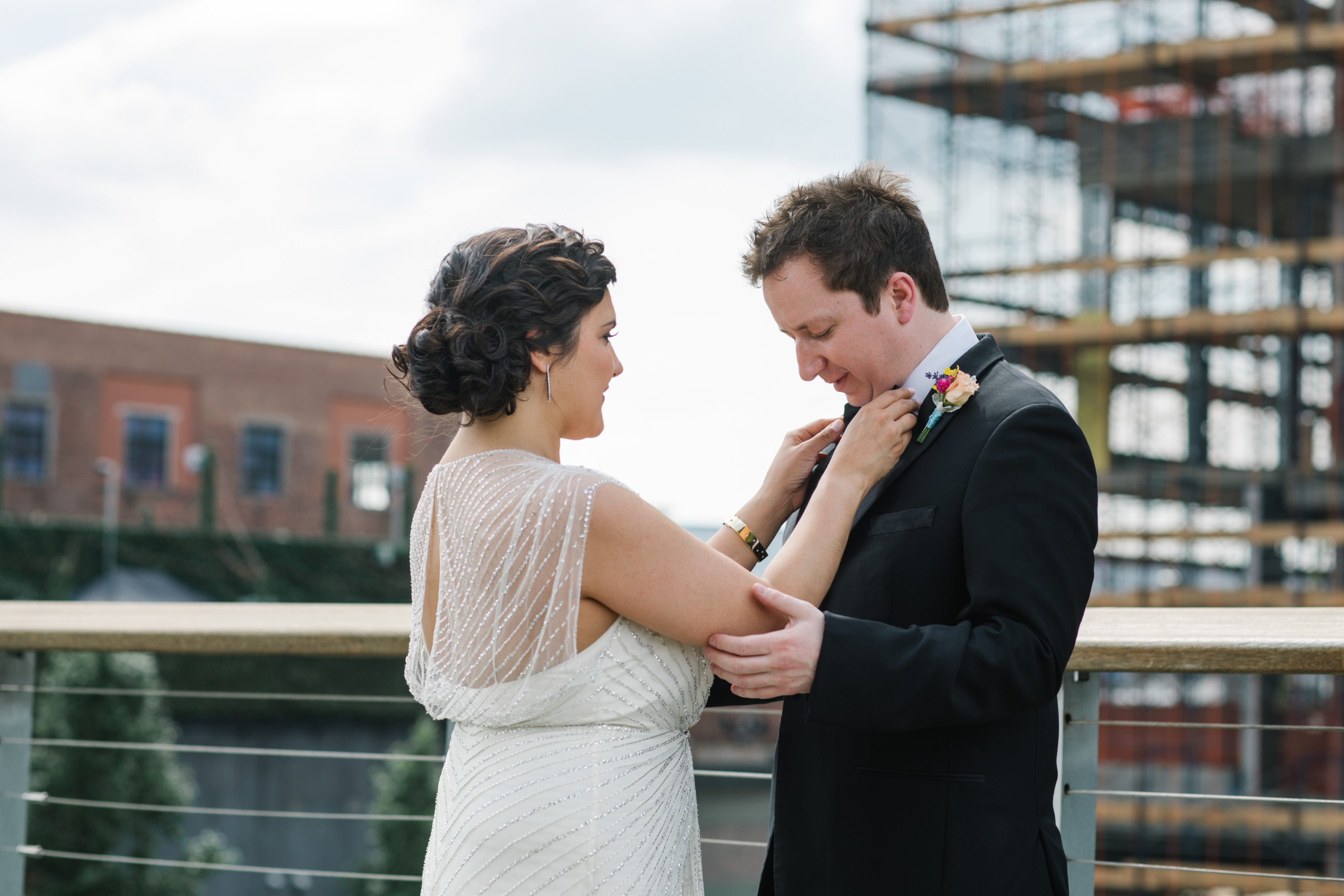 Bride with dark shiny curly hair styled with natural texture in a low chic chignon, pictured at they Wythe Hotel, Brooklyn