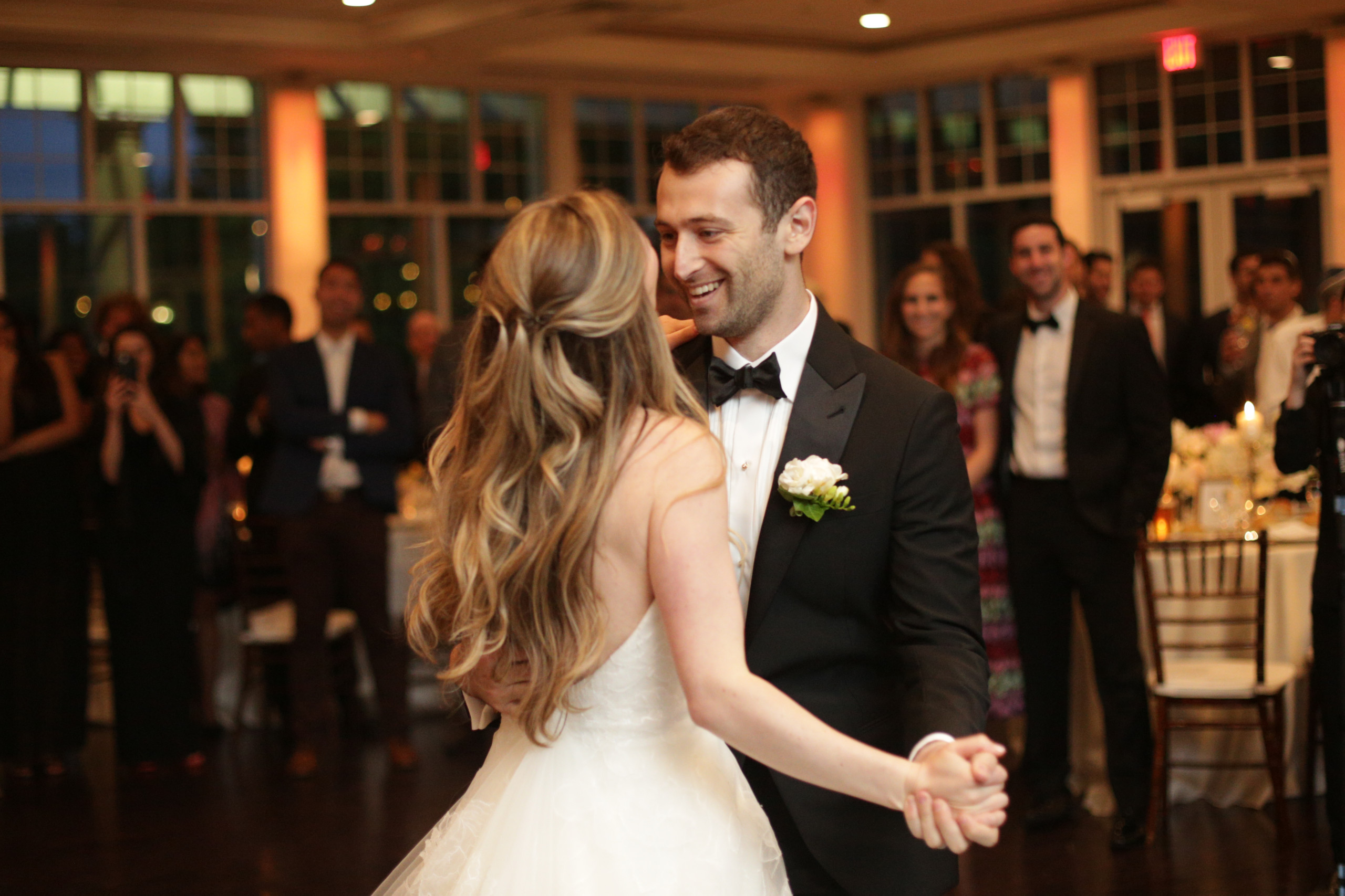 Bride with long gorgeous hair styled in waves and pulled half off of her face dances with her groom at the Stonebridge Country Club