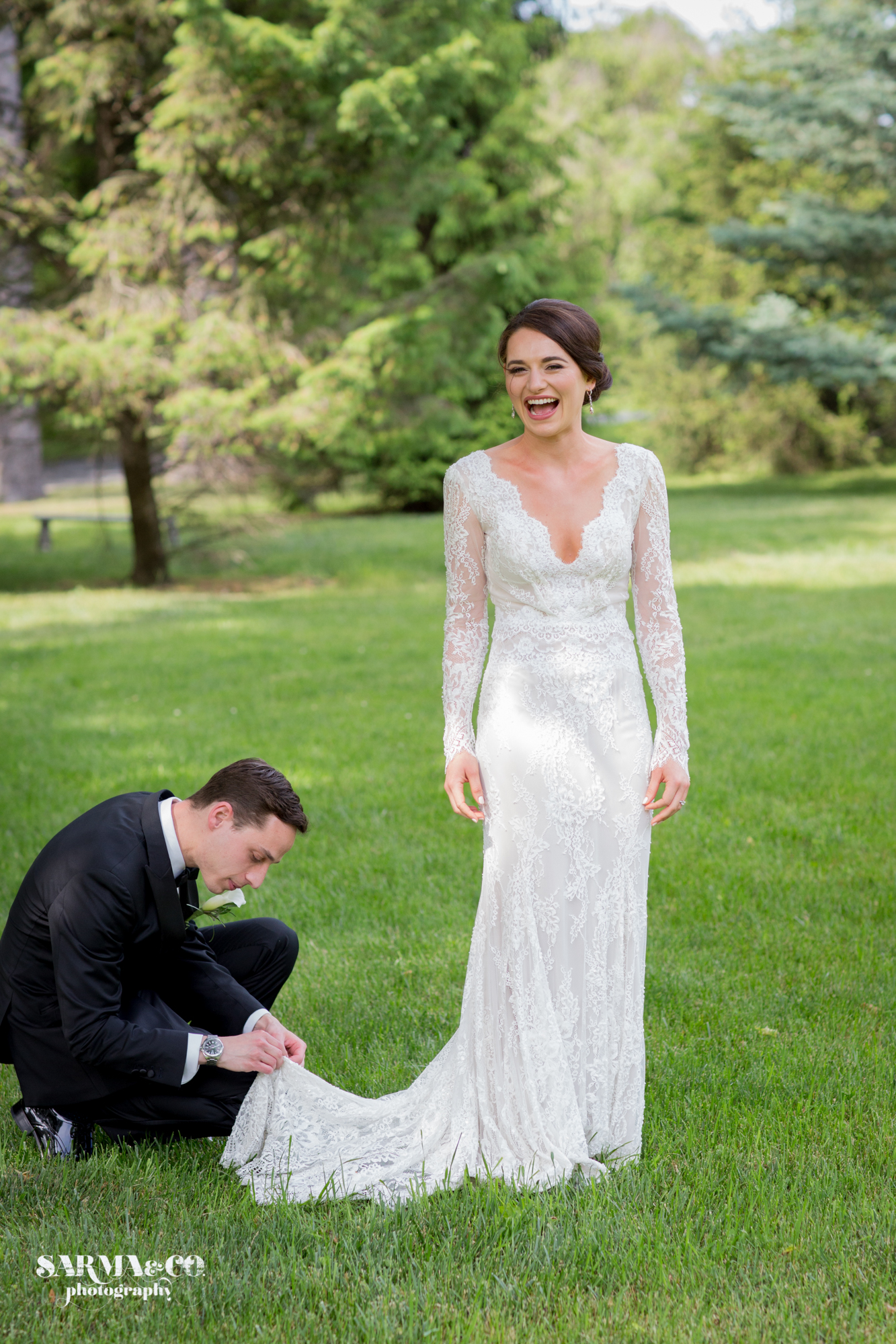 Bride with defined eyes has husband fix the hem of her dress while she laughs at Lindurst Castle in Tarrytown, New York