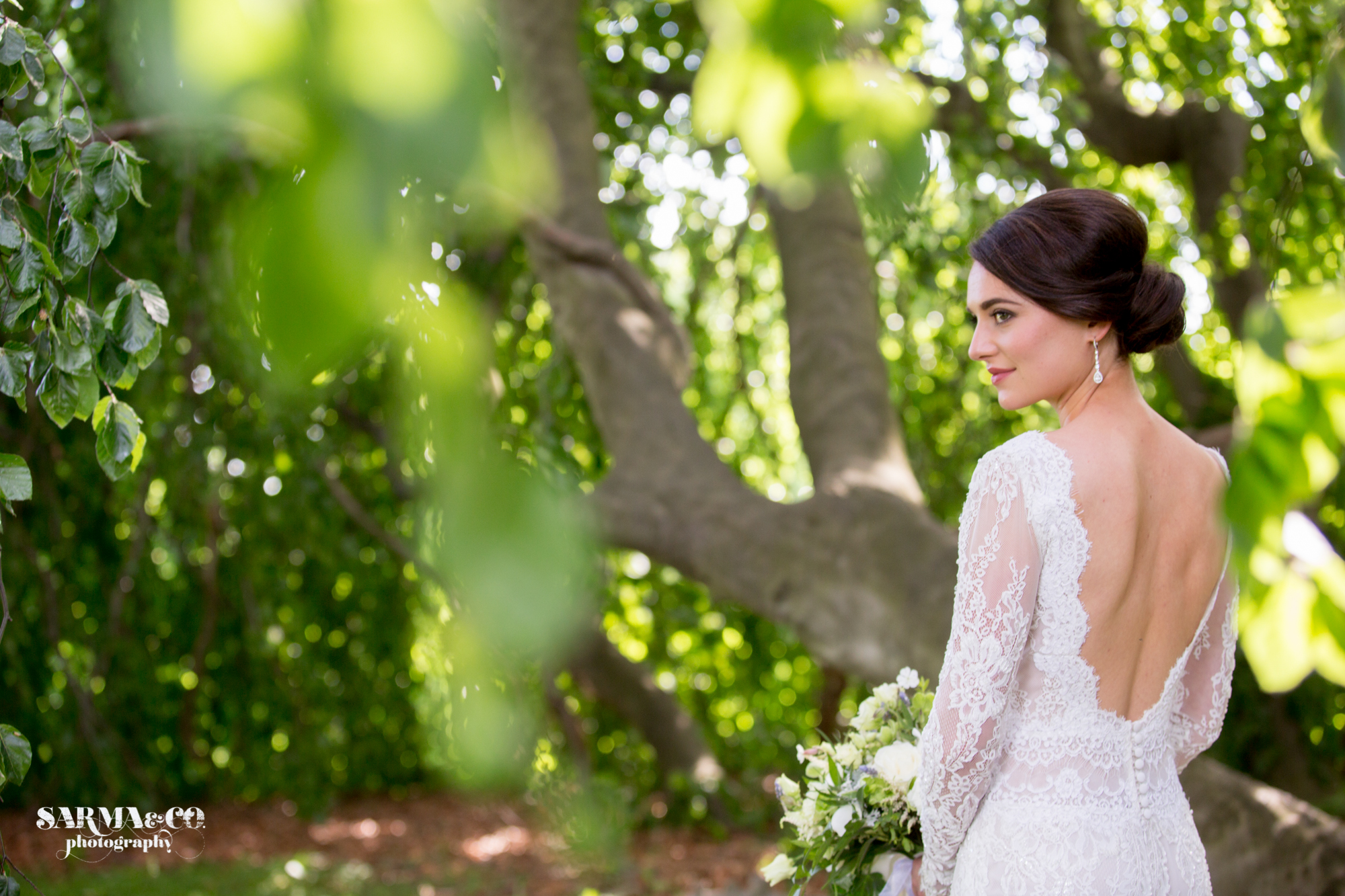 Brunette bride with backless dress, smokey eyes, and contoured cheeks poses in her backless dress for her spring wedding at the Lindhurst Castle in Tarrytown, New York